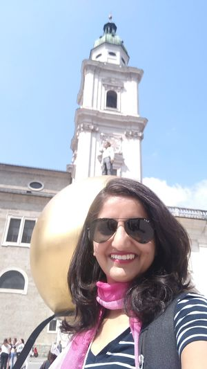 Man standing in the background on a huge golden Mozartkugel. #SelfieWithAView #TripotoCommunity