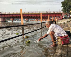 A devotee helping the prayer flowers reach their destination faster to fulfill some forgotten wish