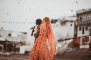A mother carrying her son in pushkar