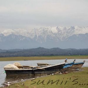 Pong lake in day view with Dhauladhar range of icy mountains.
